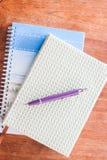 Pena e dois dos cadernos na tabela de madeira Imagens de Stock