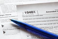 Pena e formulário de imposto azuis da renda dos E.U. Foto de Stock