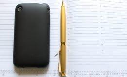 Pena e iphone dourados Foto de Stock