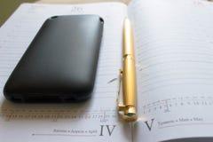 Pena e iphone dourados Fotografia de Stock