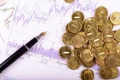 Pena e moedas no fundo dos gráficos e das cartas Fotografia de Stock Royalty Free