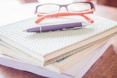 Pena e monóculos em três cadernos Imagens de Stock Royalty Free