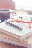 Pena e monóculos em três cadernos na cafetaria Imagem de Stock
