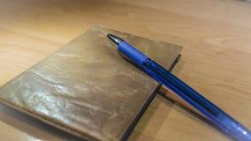 Pena e originais de esferográfica da tinta azul na mesa de madeira Imagens de Stock Royalty Free