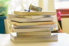 Pena e relógio de pulso colocados nos livros na tabela Fotos de Stock Royalty Free
