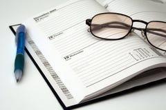 Pena e vidros em um diário Fotografia de Stock Royalty Free