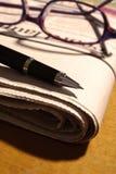Pena e vidros no jornal Imagens de Stock