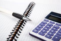 Pena em um caderno em uma pilha e em uma calculadora imagens de stock royalty free