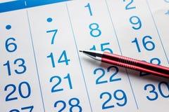 A pena encontra-se no calendário Imagens de Stock Royalty Free