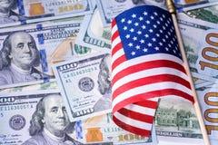 Pena, eyeglasses e gráficos Bandeira americana no fundo das notas de dólar dos E.U. Imagem de Stock