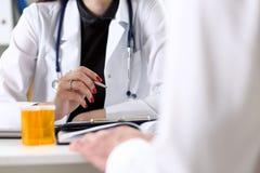 Pena fêmea da prata da posse da mão do doutor que enche a lista da história paciente fotografia de stock