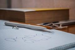 Pena, lápis, livro e caderno encontrando-se na mesa Fotografia de Stock