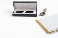 Pena na caixa com o relógio vazio do livro e de pulso de disparo Imagem de Stock Royalty Free
