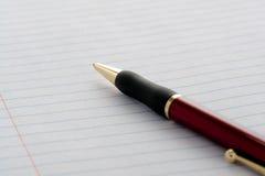 Pena na folha do papel do caderno Imagem de Stock