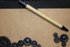 Pena no caderno com engrenagens Imagens de Stock Royalty Free