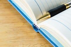 Pena no diário aberto no fundo de madeira Fotos de Stock Royalty Free