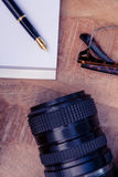 Pena no papel por vidros da câmera e do olho na mesa Imagem de Stock