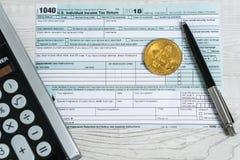 A pena, os bitcoins e a calculadora no formulário de imposto U 1040 S Declaração de rendimentos individual da renda O momento de  fotos de stock