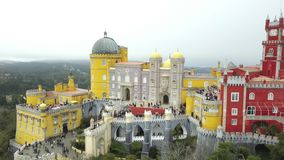 The Pena Palace, a Romanticist castle in the municipality of Sintra, Portugal, Lisbon district, Grande Lisboa, aerial view. Shot from drone. Camera moves