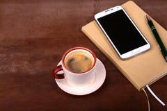 Pena vazia com uma xícara de café, telefone do caderno e de bola da mesa de escritório Conceito do negócio Foto de Stock