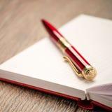 Pena vermelha que encontra-se em um caderno aberto Fotos de Stock Royalty Free