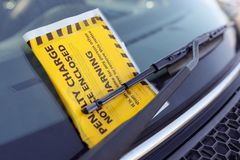 Penalty charge notice parking fine attached to windscreen. Penalty charge notice parking fine attached to car windscreen Stock Images