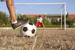 Penalty shootout. An amateur player is going to shoot a penalty to the goal on a poor soccer pitch Royalty Free Stock Photos