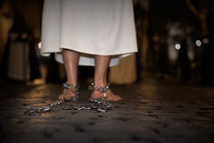 Penance. Penitent with his feet shackled and barefoot on the floor Royalty Free Stock Images