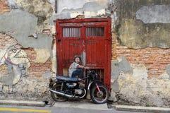 PENANG MALAYSIA - April 18, 2016: Den allmänna sikten av en vägg- `-pojke på cykel` målade vid Ernest Zacharevic Är en paien för  Arkivfoto