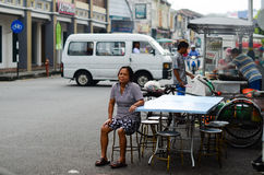 Penang, Malaysia architecture narrow streets. Penang, Malaysia - October 12, 2014: Old woman sit outdor relax on the street. Dirty architecture moldy humidity stock photography
