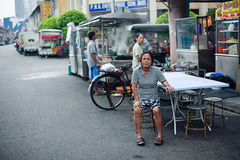 Penang, Malaysia architecture narrow streets. Penang, Malaysia - October 12, 2014: Old woman sit outdor relax on the street. Dirty architecture moldy humidity royalty free stock image