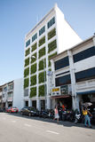 Penang, Malaysia architecture narrow streets. Penang, Malaysia - October 13, 2014: Architecture narrow streets with people on motocycle. Dirty moldy humidity royalty free stock photo