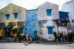 Penang, Malaysia architecture narrow streets. Penang, Malaysia - October 13, 2014: People walk on the street. Dirty architecture moldy humidity cityscape stock images