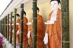 PENANG, MALAYSIA: KEK LOK SI BUDDHAS. A row of white-faced Buddha statues wearing brown robes stands in a covered arcade separated by ceramic bamboo poles at Stock Photo