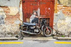 The Painting of a boy sitting on an Old Motorcycle at George Tow. Penang, Malaysia - May 21, 2016: The Painting of a boy sitting on an Old Motorcycle at George Royalty Free Stock Photos