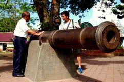 Penang, Malaysia: Touristen mit Kanone des 18. Jahrhunderts Lizenzfreies Stockbild