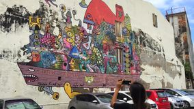 Penang, Maleisië - 20 januari: Jong toeristenmeisje die foto van de graffiti van de straatkunst op haar smartphone in George Town stock videobeelden