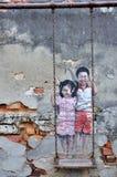 """Penang-Straßen-Kunst-""""Brother und Schwester auf einem Swingâ€- Stockfoto"""