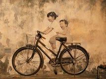 Penangmuurschildering, Jonge geitjes op Fiets Stock Afbeeldingen