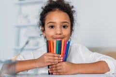 penas coloridas de feltro da criança terra arrendada afro-americano adorável e vista da câmera Fotografia de Stock Royalty Free