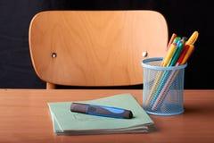 Penas coloridas em uma cesta azul do metal na mesa na escola Fotos de Stock