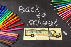 Penas coloridas, lápis, título de volta à escola escrita pelo giz e o ônibus escolar tirado em pedaços de papel em chalkboar Fotos de Stock