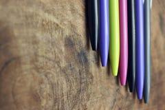 Penas coloridas na madeira imagem de stock