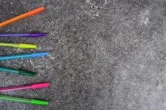 Penas coloridas no fundo cinzento escuro do grunge foto de stock