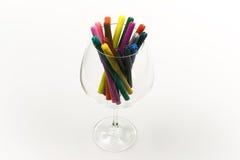 Penas coloridas no vidro isolado no backgroun branco Fotografia de Stock