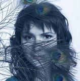 Penas da mulher nova e do pavão Imagens de Stock Royalty Free
