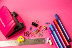 Penas de feltro, lápis, grampos de cores diferentes em um backgrou cor-de-rosa imagem de stock royalty free