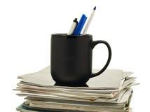 Penas em uma caneca de café sobre a pilha de compartimentos Imagem de Stock Royalty Free