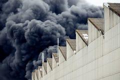 Penas pretas do fumo de um fogo industrial tóxico acidental como visto da atrás de uma construção da fábrica fotografia de stock royalty free