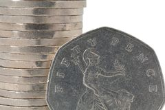 50 pence. A 50 pence piece in front of a pile of coins Royalty Free Stock Photos
